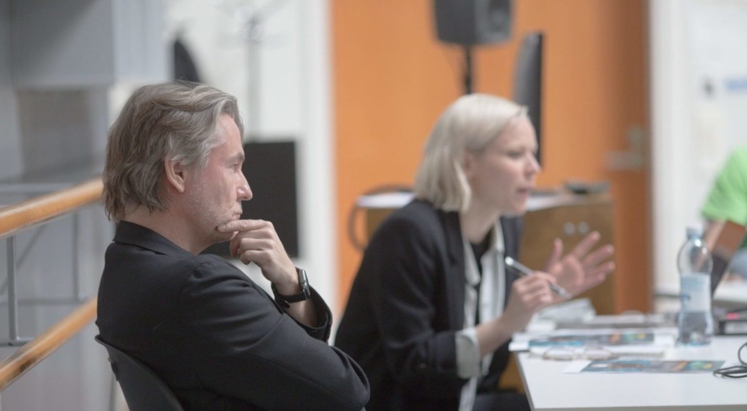 Man and woman in black suits sitting in front of a table