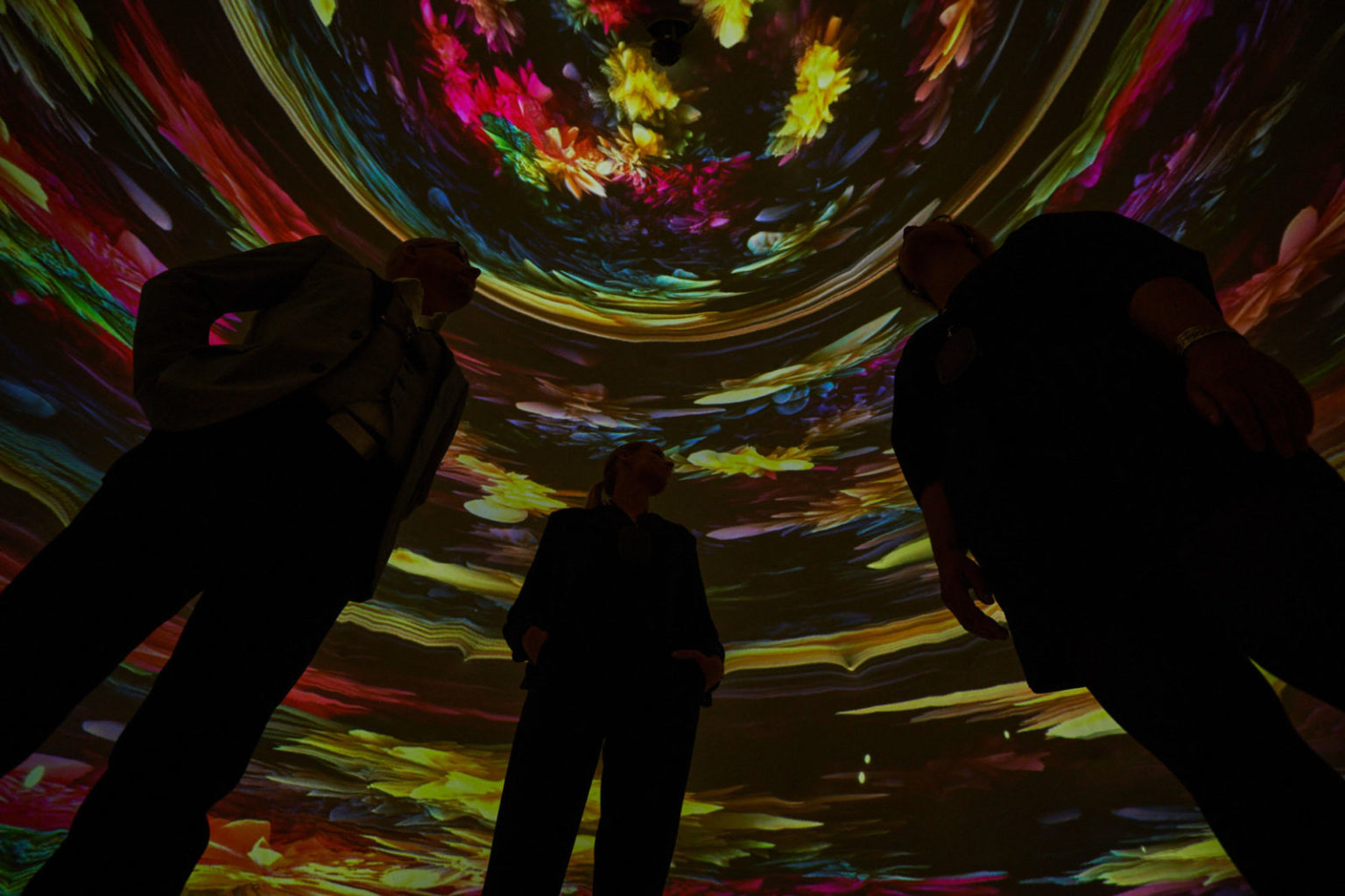 In the image, three people standing in a semicircular dome, surrounded by digital and floral patterns in vibrant colors.